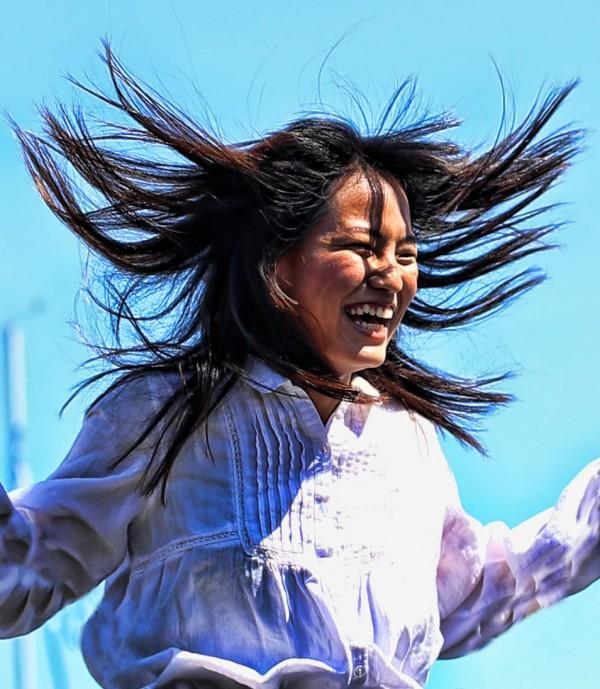 jovem mulher sorrindo cabelos esvoaçantes