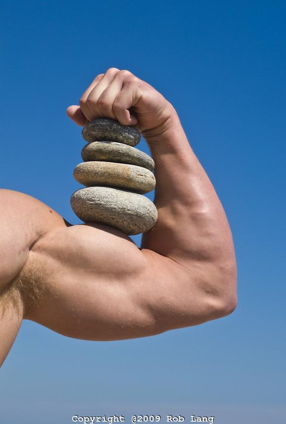 man-holding-stones-on-his-big-bicep