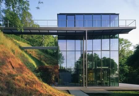 """Apesar do nome, a House R 128 está mais para um prédio do que para uma casa, já que possui quatro apartamentos. Um de seus destaque é a """"sustentabilidade"""": as paredes de vidro permitem que a luz do sol seja bem aproveitada durante o dia, e painéis solares garantem energia à noite; a casa aproveita energia geotérmica para resfriamento e aquecimento do ambiente, conforme a necessidade; por fim, é uma casa """"reciclável"""", já que sua estrutura pode ser facilmente desmontada e reaproveitada"""