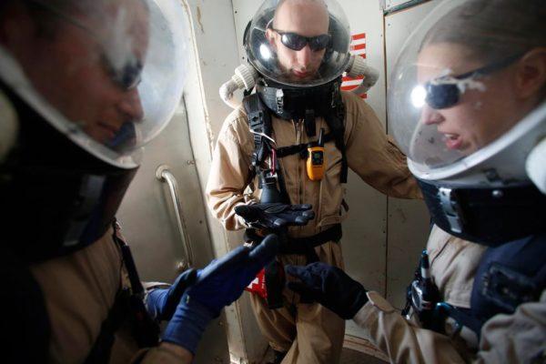 Pesquisadores aguardam em uma câmara, com seus trajes espaciais, antes de se aventurarem coletando amostras geológicas no deserto