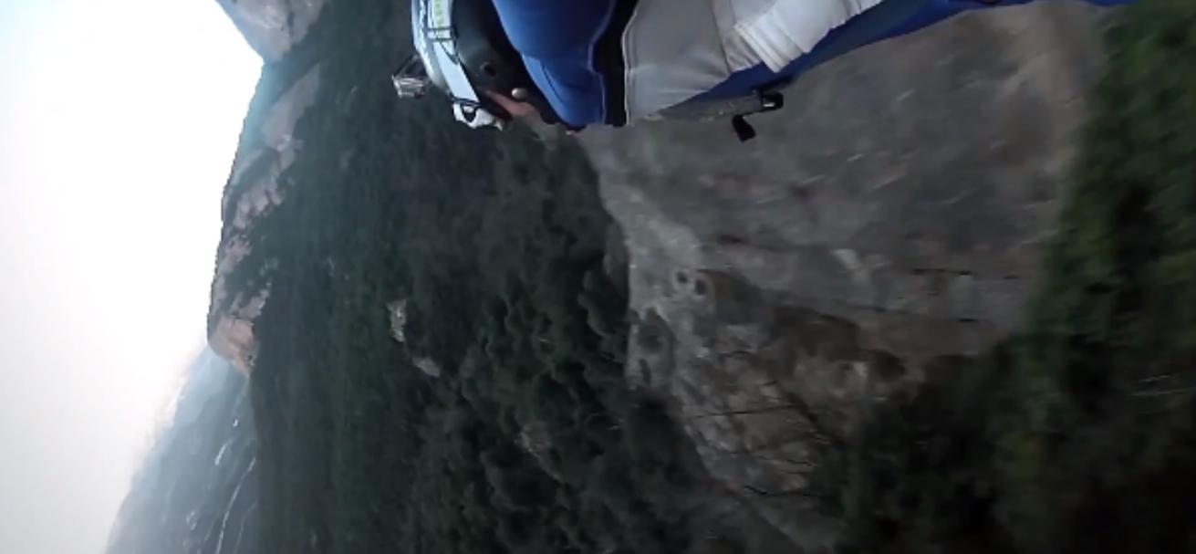 Homem em traje planador voa por dentro de caverna estreita