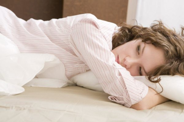 attractive thoughtful brunette curl woman with a pillow on the b