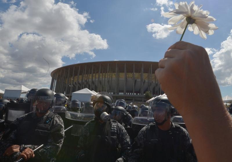 Manifestantes levantam flores para mostrar o intuito pacífico do protesto contra os gastos públicos com a Copa do Mundo em Brasília, 2013