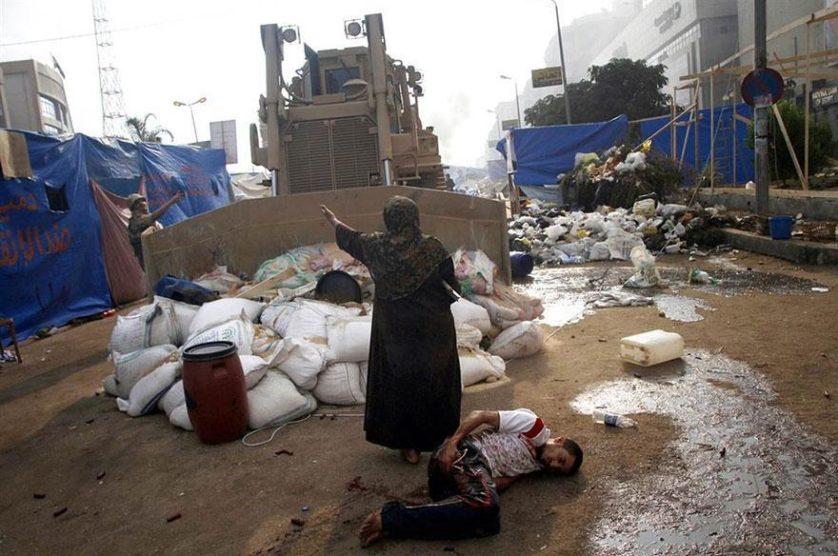 Mulher defende um manifestante ferido de um veículo militar no Egito, 2013