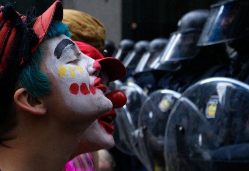 Manifestantes vestidos como palhaços entretêm guardas em uma reunião do G20 em Toronto, Canadá, 2010
