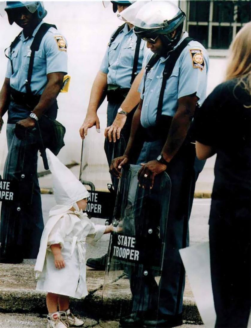 Garoto com vestes KKK (Ku Klux Klan) vê seu reflexo em um escudo policial na Geórgia, EUA, 1992