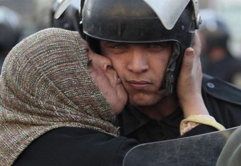 Mulher egípcia beija um policial durante a revolução contra o governo Mubarak no Egito, 2011