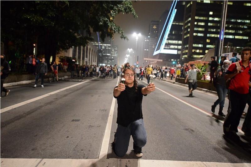 Manifestante oferece flores para tropa de choque durante protestos contra o aumento da tarifa no transporte público em São Paulo, 2013