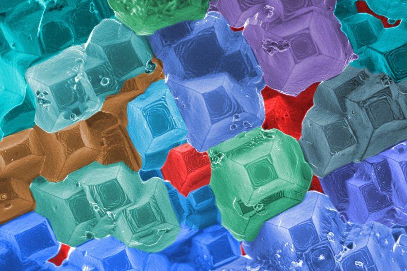 Para encontrar, e possivelmente prevenir, pontos fracos em materiais sob estresse extremo, como os que estão no coração de um reator nuclear, os cientistas do laboratório estão combinando imagens detalhadas macroscópicas e microscópicas. Esta imagem colorida mostra uma liga de alto-cromo à base de níquel. A sua superfície foi gravada quimicamente para revelar planos cristalográficos facetados em regiões do dano microestrutural localizado. Através de sua pesquisa, os cientistas estão entendendo como danos em ligas metálicas evoluem. Esta informação pode ajudar a identificar mecanismos de falha, melhorar a confiabilidade e prolongar a vida útil de reatores