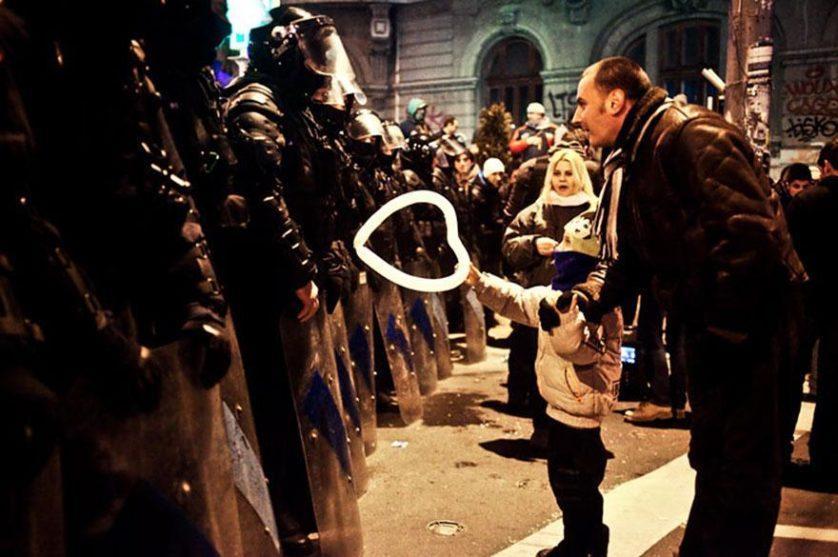 Menino oferece um balão em forma de coração para a polícia em Bucareste, Romênia, 2012