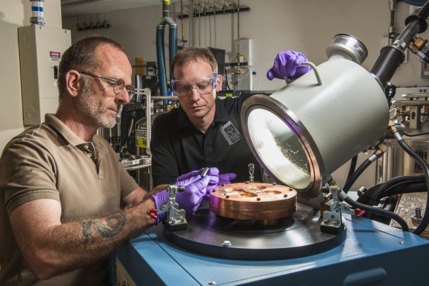 Mark Reece, à esquerda, e Don Susan examinam um novo botão de liga de memória que eles removeram de um arco-aparelho de fusão. Várias novas ligas têm sido desenvolvidas no Sandia