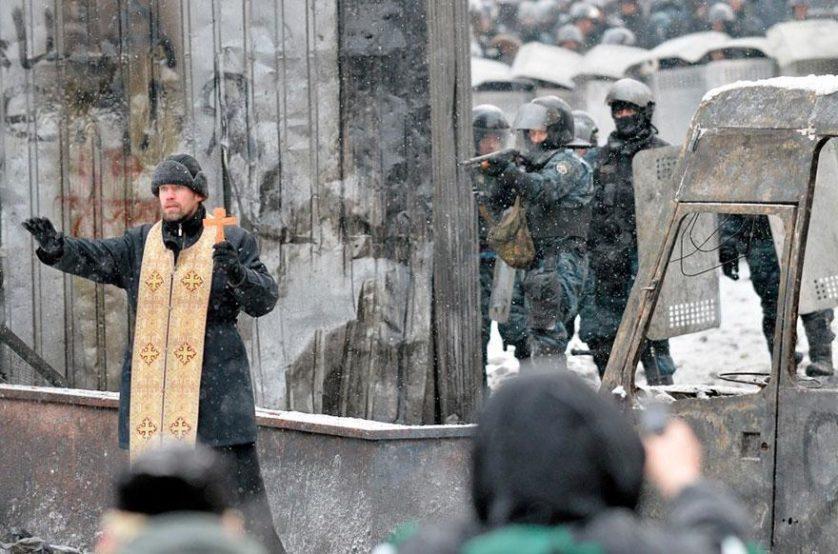 Padre ortodoxo tenta evitar um confronto entre manifestantes e polícia em Kiev, Ucrânia, 2014