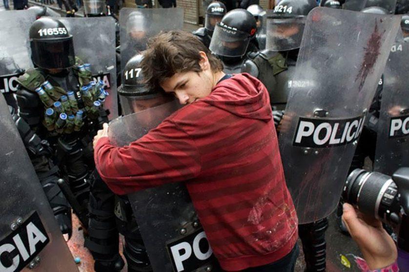 Um estudante protestando pela reforma da educação abraça um policial em Bogotá, Colômbia, 2011