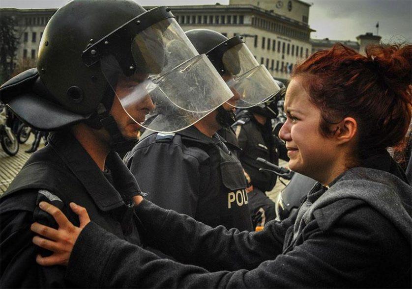 Tropa de choque e manifestantes choram juntos em Sófia, Bulgária, 2013