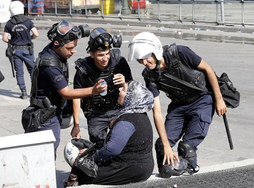 Polícia ajuda uma mulher atingida por gás lacrimogêneo em Ancara, Turquia, 2013