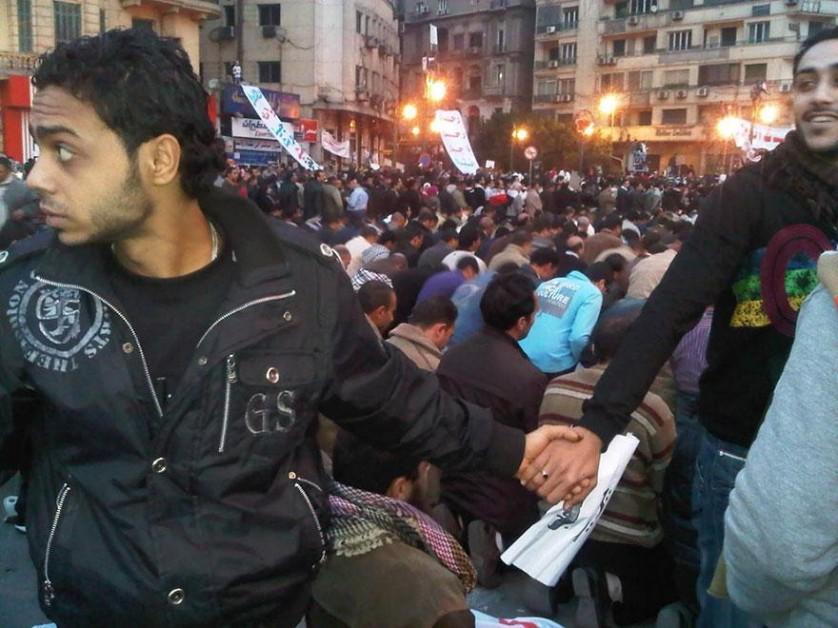 Cristãos protegem muçulmanos que rezam durante a revolta no Cairo, Egito, 2011