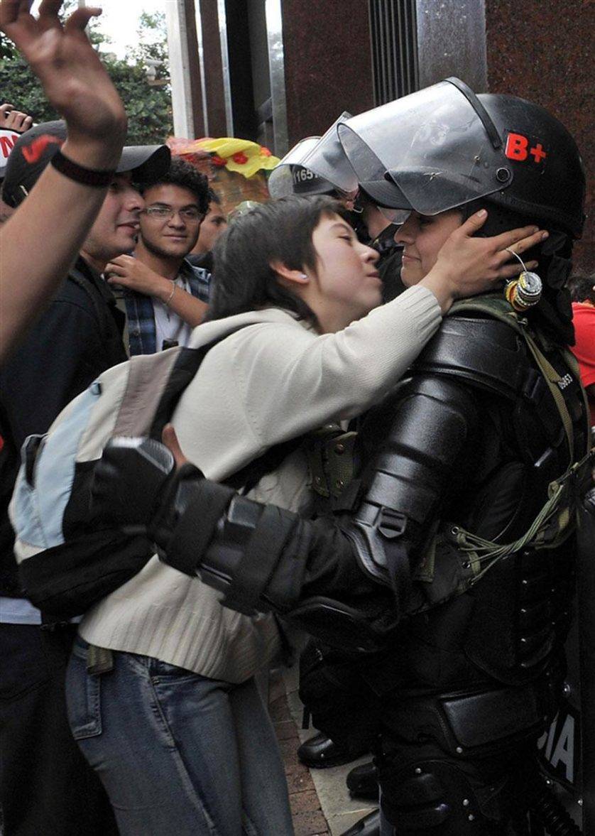 Estudante protestando por reforma na educação se inclina para beijar uma policial em Bogotá, Colômbia, 2011