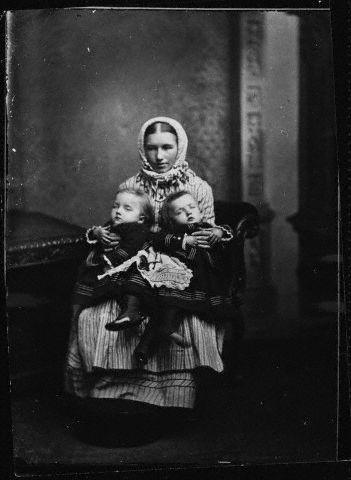 Woman Holds Siamese Twins