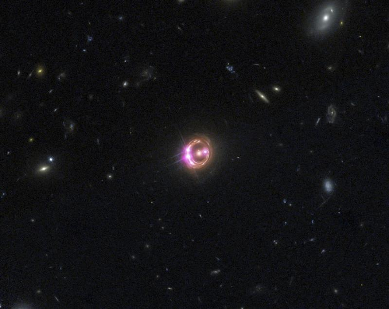 Multiple images of a distant quasar are visible in this undated combined view from NASA's Chandra X-ray Observatory and the Hubble Space Telescope