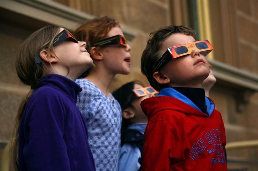 """Crianças usam óculos de proteção enquanto assistem a um eclipse solar parcial no Observatório de Sydney, na Austrália, em 29 de abril de 2014. Australianos puderam ver um eclipse com até dois terços do sol obscurecido pela lua. Um eclipse solar anular, também conhecido como """"círculo de fogo"""", foi visível a partir de uma pequena região da Antártida."""