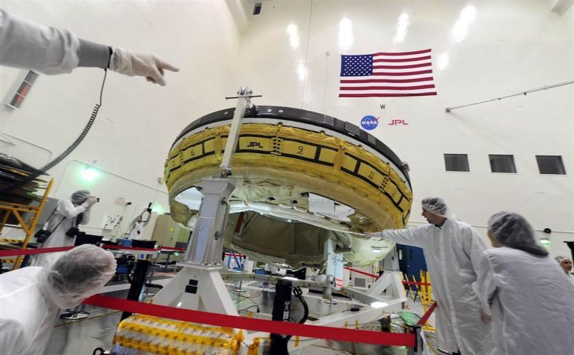 """Jornalistas vestidos com trajes especiais admiram um veículo de teste em forma de disco voador dentro da sala do Laboratório de Propulsão a Jato da NASA em Pasadena, na Califórnia (EUA), em 9 de abril. O """"Desacelerador Supersônico de Baixa Densidade"""" da agência espacial norte-americana é projetado para permitir que grandes cargas desembarquem com segurança na superfície de Marte e outros corpos planetários com atmosferas, incluindo a Terra."""
