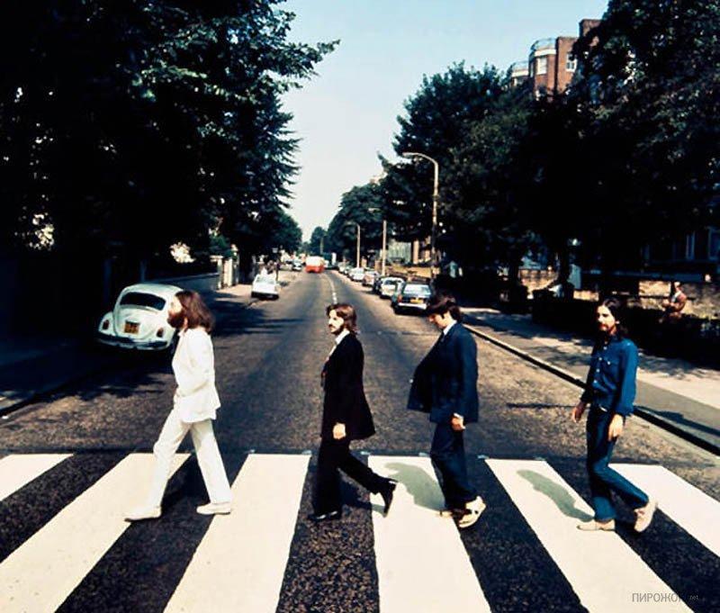 """Os Beatles andando na direção oposta durante a sessão de fotos para a capa do álbum """"Abbey Road"""""""