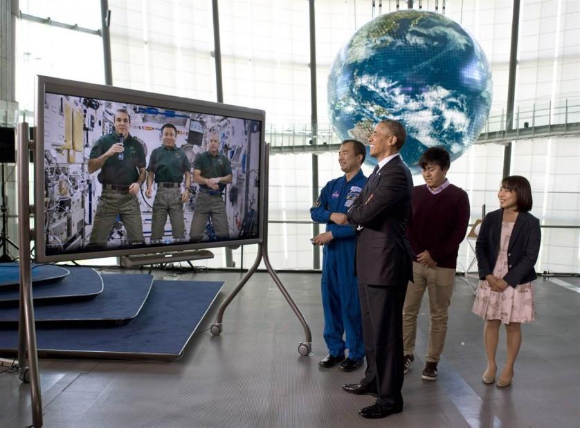 """O presidente dos EUA Barack Obama escuta uma mensagem pré-gravada feita na Estação Espacial Internacional enquanto participa de um evento no Museu Nacional de Ciência Emergente e Inovação, conhecido como Miraikan, em Tóquio, no Japão, no último 24 de abril. O fundo mostra """"Geo-Cosmos"""", um globo coberto com painéis de LED que exibem imagens atuais de satélite da Terra."""