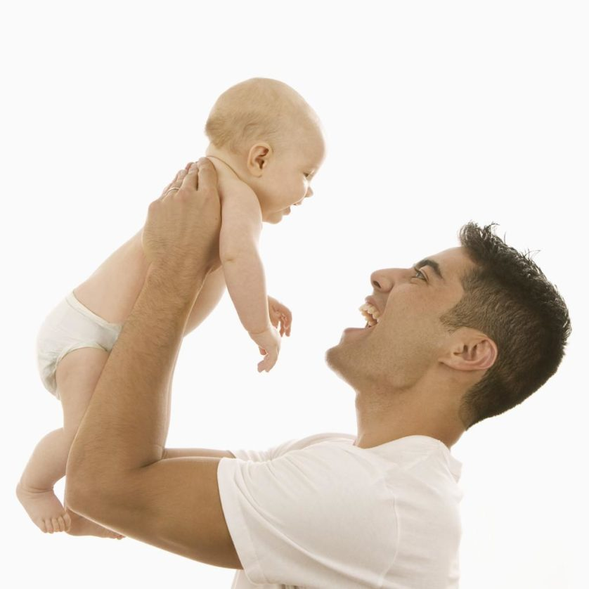 Man Holding Up an Infant