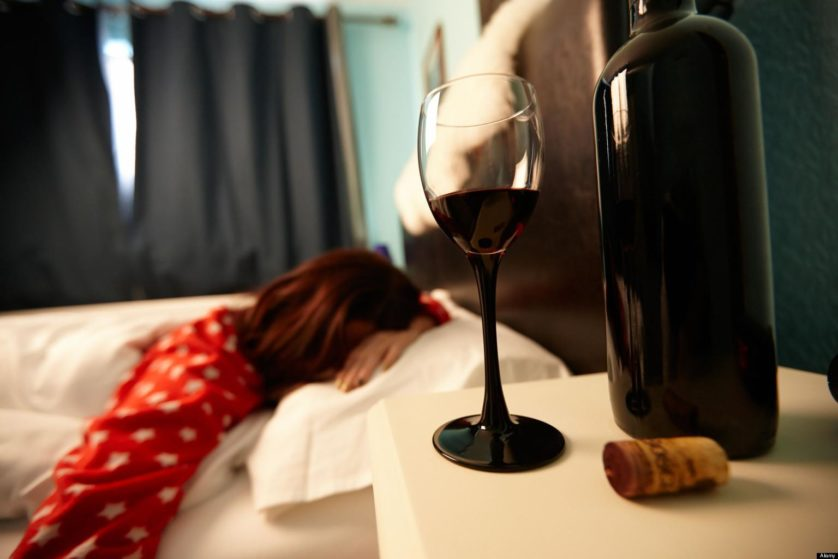 half full glass of wine on bedside table of early twenties woman in bed in a bedroom