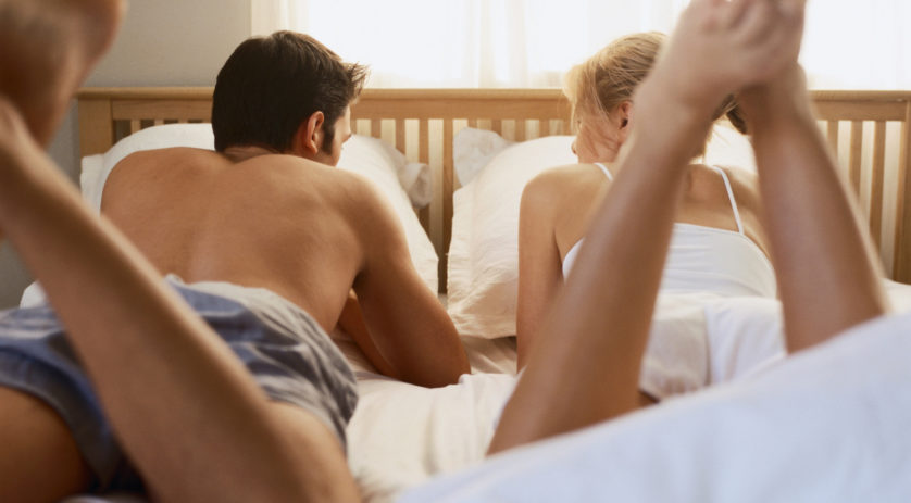 Couple lying and talking in bed, rear view