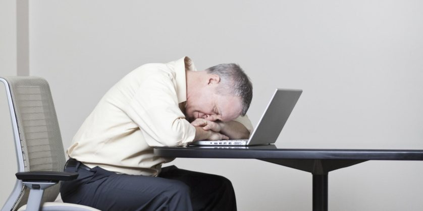 Caucasian businessman sleeping on laptop