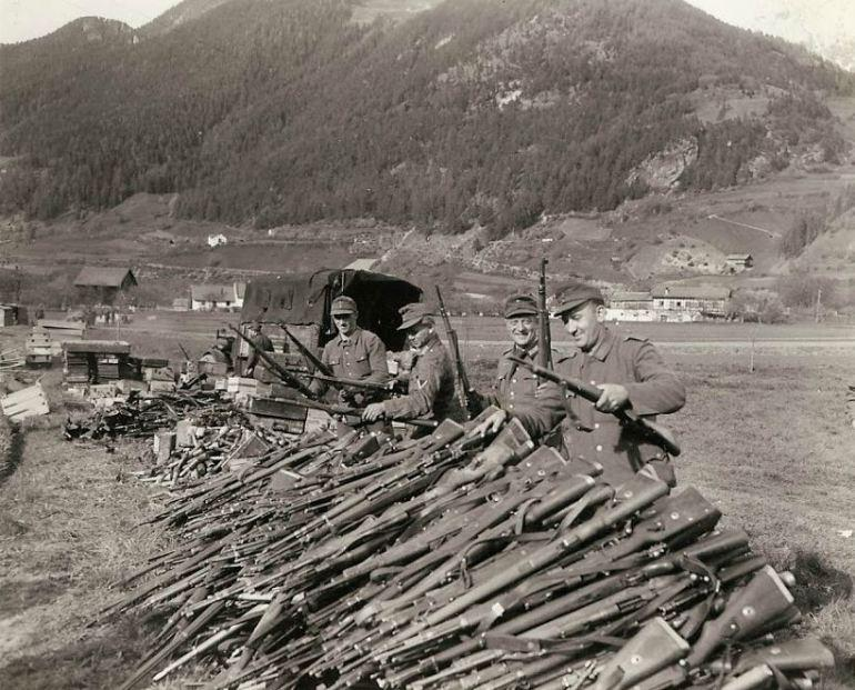 """A rendição do 19º Exército. Com a capitulação final da Alemanha para os Aliados, os soldados alemães que levantaram armas por mais de cinco anos contra quase toda a Europa e os EUA renderam seus rifles para os norte-americanos perto de Landeck, na Áustria. Eles parecem felizes com o """"fim"""". Granadas de mão e outros equipamentos podem ser vistos empilhados além dos rifles."""