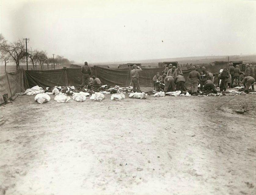 Soldados norte-americanos e alemães mortos em um cemitério antes do enterro, em um local desconhecido. Cada corpo foi colocado em uma capa de colchão. Prisioneiros alemães podem ser vistos fazendo o trabalho de cavar as sepulturas e colocando os corpos dentro delas.