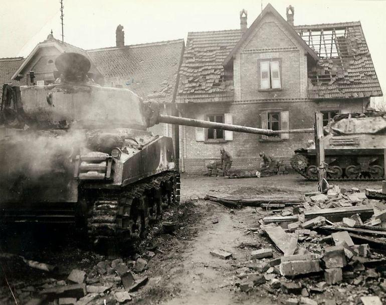 Um tanque destroier passando por um tanque americano que foi nocauteado durante uma batalha quando os americanos retomaram a cidade. Entre os dois veículos blindados, dois médicos coletam o corpo de um soldado americano morto na luta.