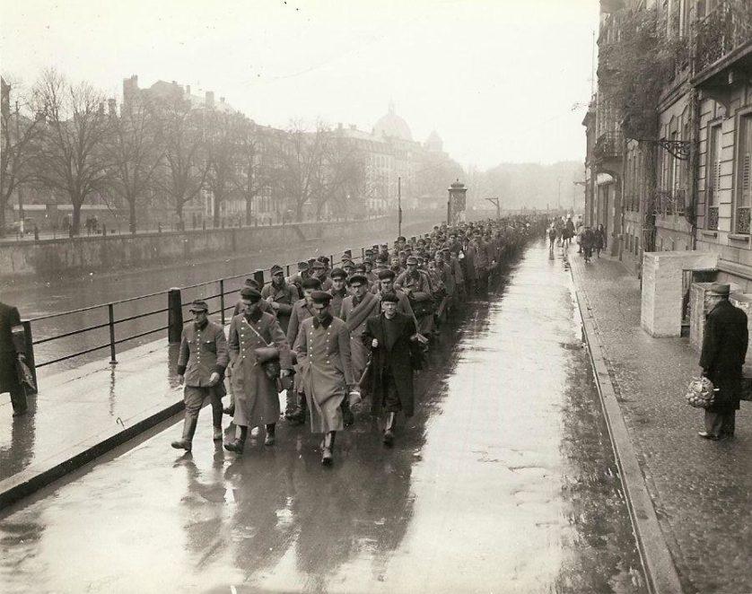 Prisioneiros de guerra da Polícia Militar alemã e agentes da Gestapo na cidade de Estrasburgo são levados a 3ª Divisão de Infantaria. Os prisioneiros estão sendo escoltados pelas Forças Francesas do Interior.
