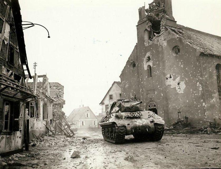 Um M-10 Tank Destroyer do 636º Batalhão de Tank Destroyer, apoiando o 143º Regimento de Infantaria, 36ª Divisão, em Rohrwiller, 4 de fevereiro de 1945. O extenso dano à igreja da cidade foi provavelmente feito por explosões.