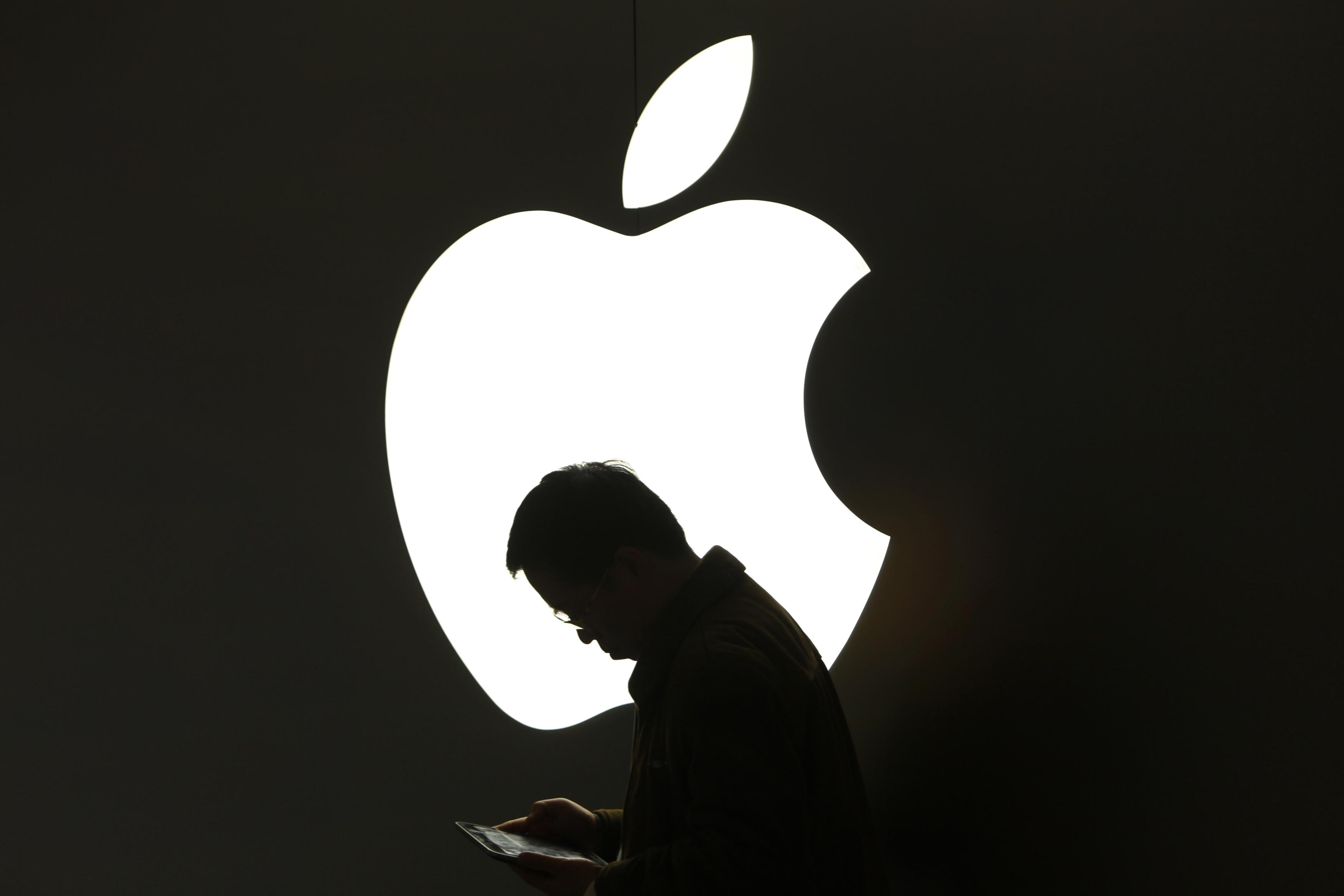 A man looks at his Apple iPad in front an Apple logo outside an Apple store in downtown Shanghai