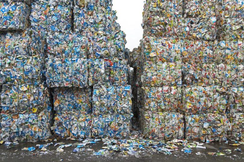 Embalagens de bebidas de papelão, polietileno e alumínio comprimidas em uma fábrica especializada em reciclagem de papel. Durante o processo de reciclagem, cada material é isolado. O papelão se torna produtos como toalhas de papel e papel higiênico. O alumínio e o polietileno são enviados para outros lugares
