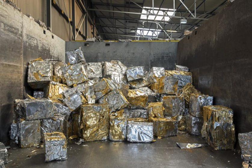 Recortes de alumínio são compactados em grandes blocos atados com laca de ouro usada para embalagem de latas de cerveja. Na fundição de uma reciclagem, a laca é queimada e o alumínio fundido é reconvertido em novos blocos que podem ser usados para produzir novas latas