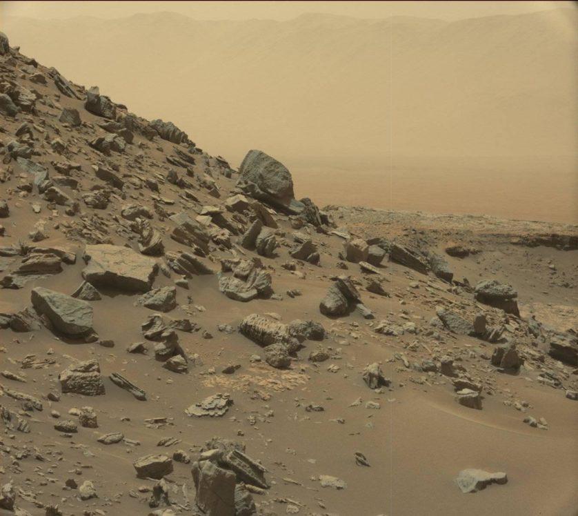 Essa imagem mostra uma encosta inclinada na região de Murray Buttes. A borda da cratera Gale, onde Curiosity desembarcou em 2012, é visível à distância através da névoa empoeirada