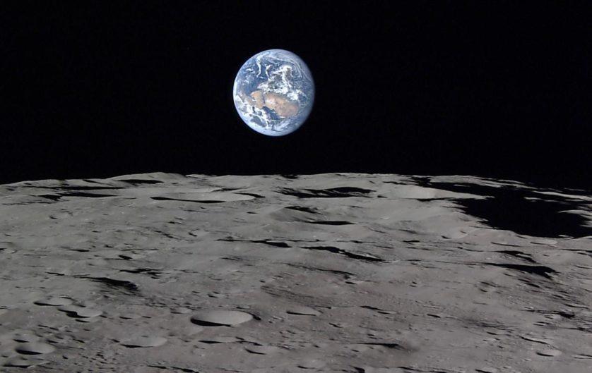 O lado iluminado da Terra brilha como uma bola de gude azul sobre a planície lunar.
