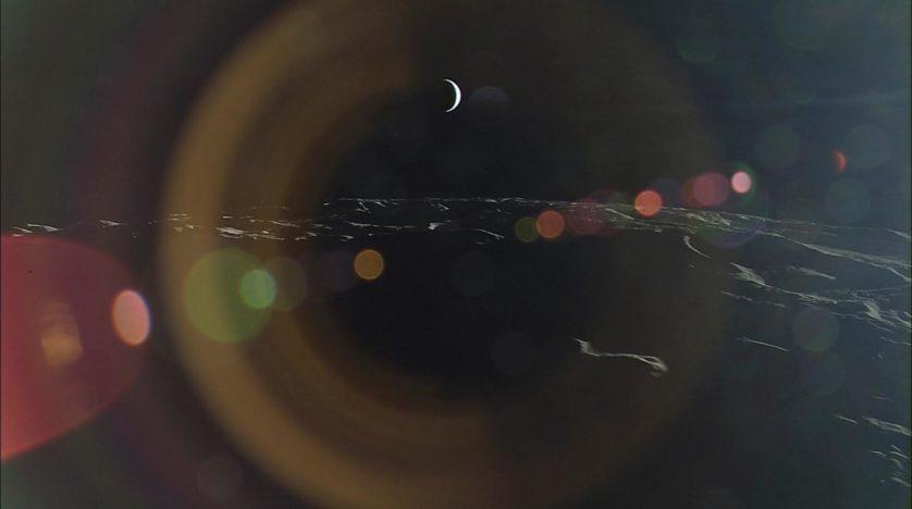 Uma lente lança cores em uma Terra crescente vista da lua.