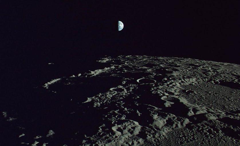 A Terra paira acima de crateras lunares sombreadas.