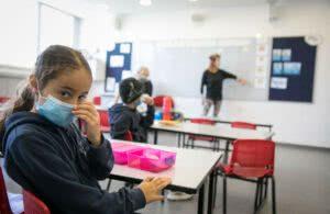 Criança com máscara facial na sala de aula